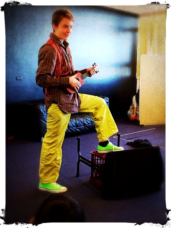 Boy in brightly coloured clothing playing a Ukelele.