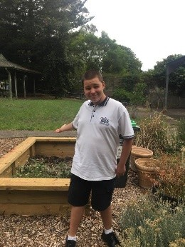 One of our students with the garden beds we use for our Eco garden.